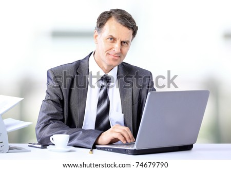 Businessman sitting at desk and working with laptop computer.