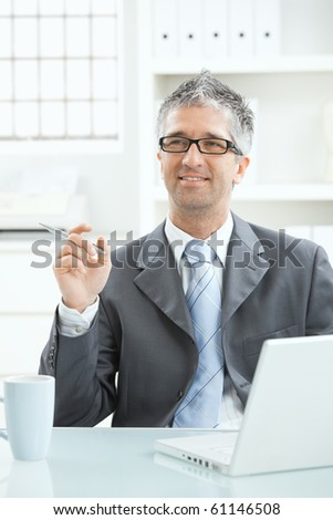 Businessman sitting at desk having a good idea, holding pen in hand, looking up smiling.
