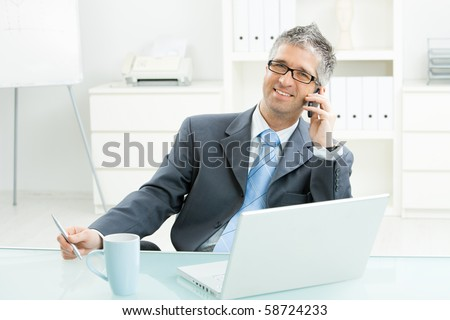 Businessman sitting at desk in bright office, talking on mobile phone and smiling.