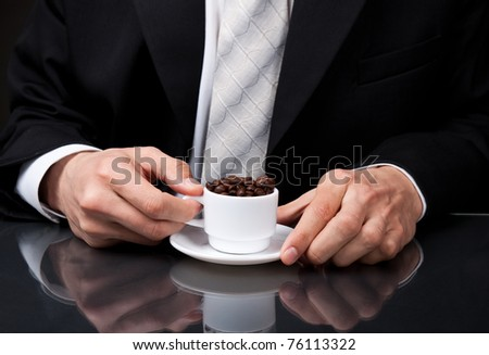 Businessman sitting at desk in office and holding cup of hot coffee close up, drinking coffee concept.