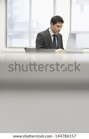 Businessman sitting at desk in office and using laptop