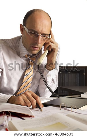Businessman sitting at desk in office being busy on the phone and studying papers.