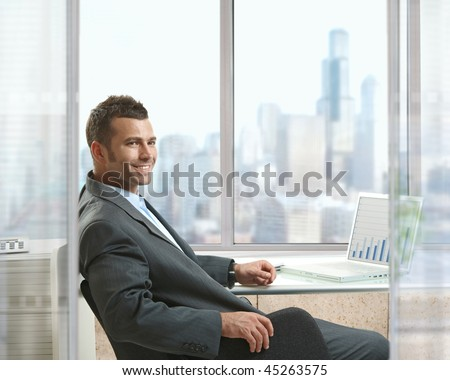 Businessman sitting at desk in office, working with laptop computer, looking back, smiling.