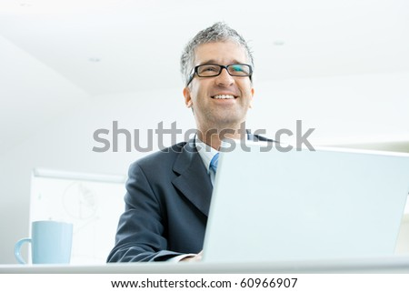 Businessman sitting at desk working on laptop computer, smiling and looking at camera.