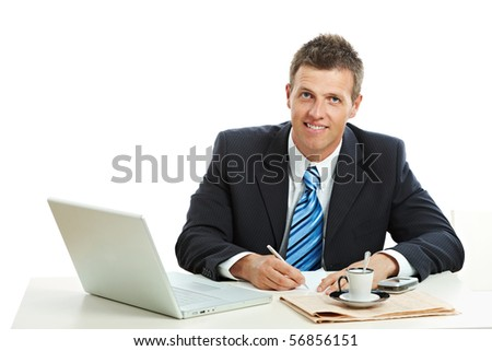 Businessman sitting at desk, writing notes on paper, smiling. Isolated on white background.