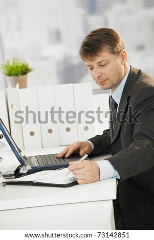 Businessman sitting at desk, writing notes to organizer and using laptop computer.?