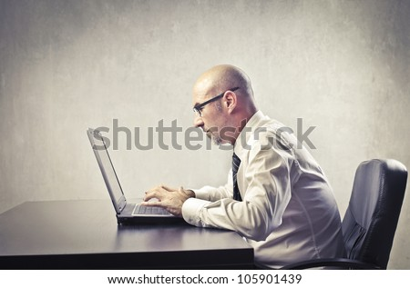 Businessman sitting at his desk and using a laptop
