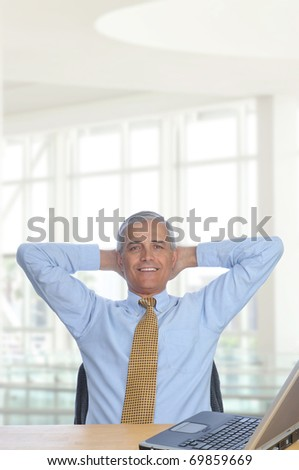 Businessman sitting at his desk in a modern office building with hands behind his head. Vertical Format