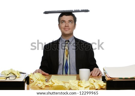 Businessman sitting at his desk looking up at the keyboard he is balancing on his head. Isolated against a white background.
