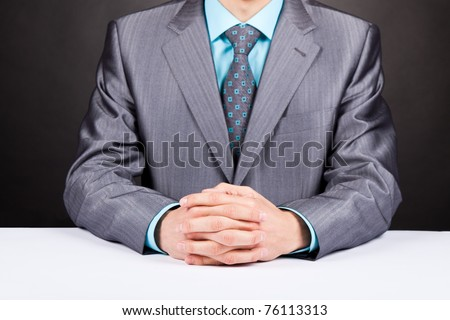 businessman sitting at his desk over gray background