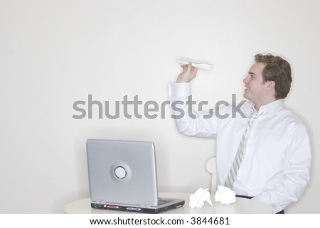 Businessman sitting at his desk throwing a paper airplane for his own amusement with a laptop on his desk - stock photo