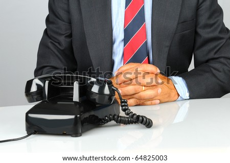 Businessman sitting at his desk with retro telephone waiting for a call. Close up shot of torso and desk only. Man has his hands together on desk in front of phone. Horizontal format.