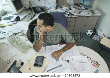 Businessman sitting at messy desk