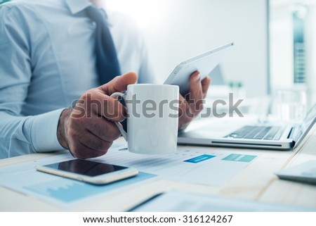 Shutterstock Businessman sitting at office desk having a coffee break, he is holding a mug and a digital tablet