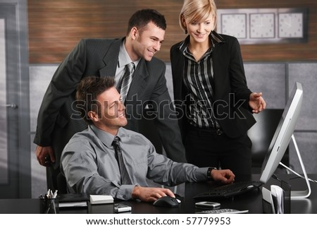 Businessman sitting at office desk, looking at screen together with colleagues, smiling.?