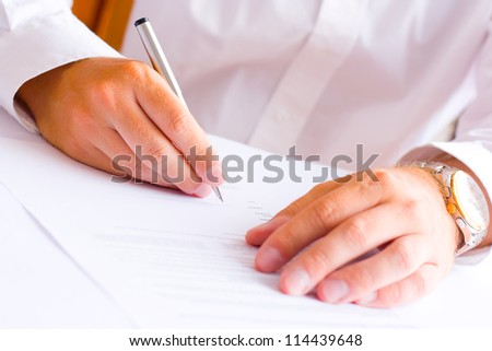 Businessman sitting at office desk signing a contract - shallow focus on signature