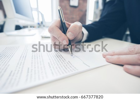 Businessman sitting at office desk signing a contract with shallow focus on signature. #667377820