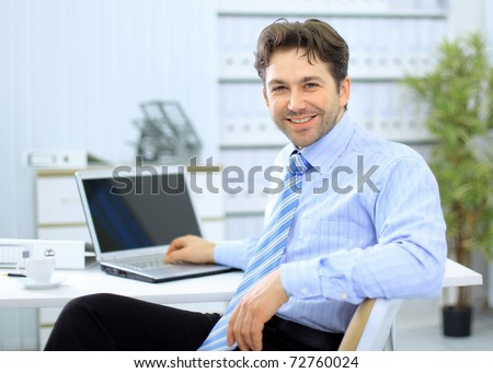 Businessman sitting at office desk working on laptop computer - stock photo