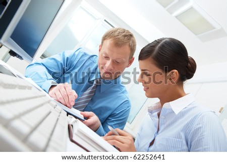 Businessman sitting at table and writing, young businesswoman sitting and looking at him