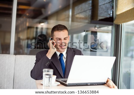 Businessman sitting at table in cafe and working - stock photo