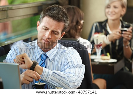 Businessman sitting at table in cafe, waiting for somebody looking at his watch. Young women having sweets in the background.