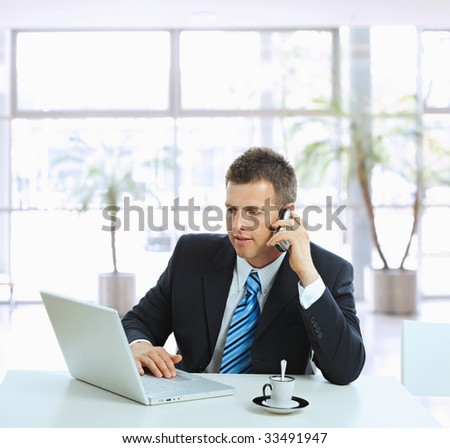 Businessman sitting at table in office hall, talking on mobile phone and using laptop computer.