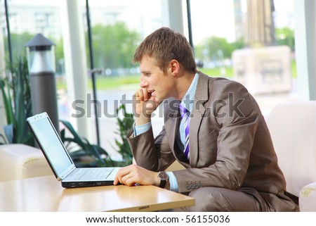 Businessman sitting at table in office hall, talking on mobile phone and using laptop computer