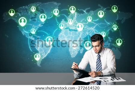 Businessman sitting at table with social media connection symbols on the world map