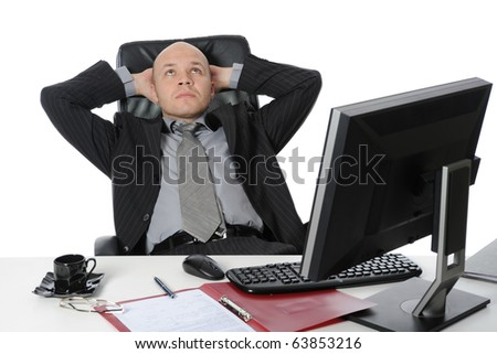 Businessman sitting before a computer. Isolated on white background