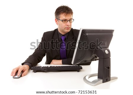 Businessman sitting behind desk at work, looking at monitor, over white background