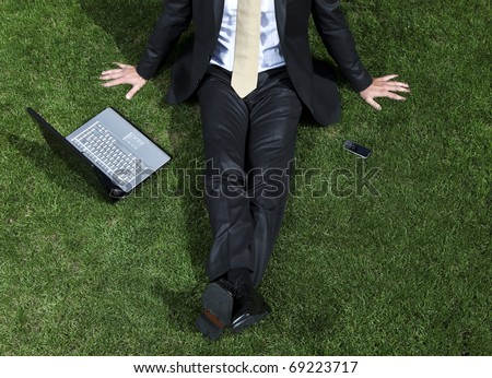 businessman sitting in a park with his laptop