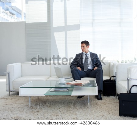 Businessman sitting in a waiting room and using a laptop