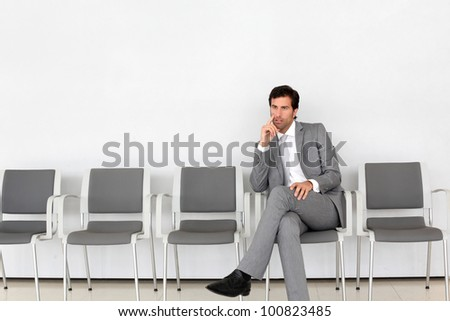 Businessman sitting in airport waiting room - stock photo