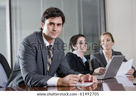 Businessman sitting in boardroom, female co-workers working in background