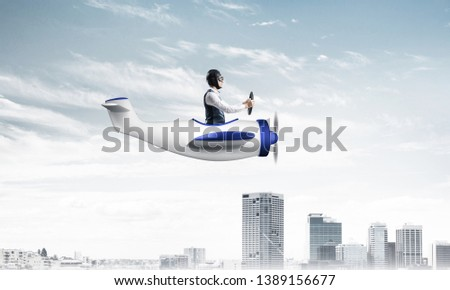 Businessman sitting in cabin of small airplane and holding steering wheel. Funny man in aviator hat and goggles driving propeller plane above city. Modern metropolis with high buildings and towers #1389156677