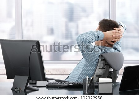 Businessman sitting in chair, resting in office.