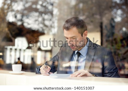Businessman sitting in coffee shop, signing contract