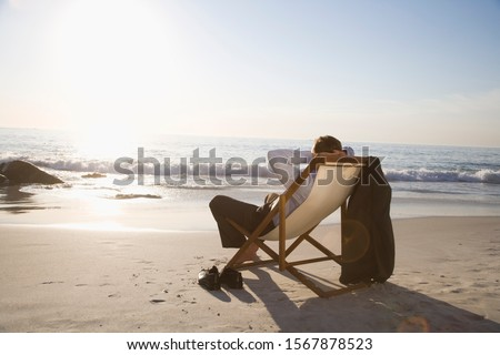 Businessman sitting in deck chair at beach