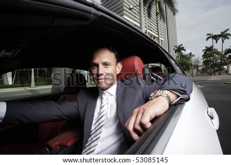 Businessman sitting in his car and smiling