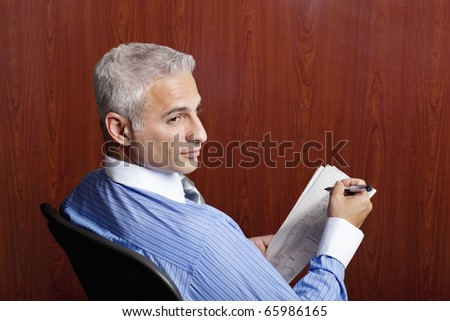 newspaper stock quotes. stock photo : Businessman sitting in his office looking at stock quotes in
