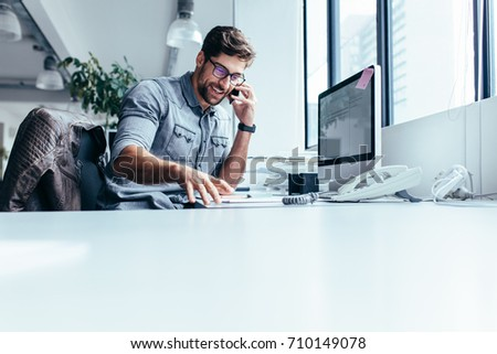 Businessman sitting in office and talking on mobile phone. Young businessman making call on his smartphone.