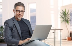 Businessman sitting in office working with laptop computer. Business portrait of older man.