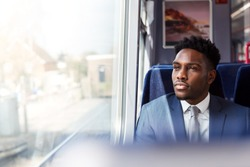 Businessman Sitting In Train Commuting To Work Looking Out Of Window