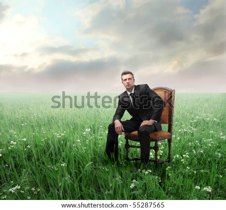 Businessman sitting on a chair on a green meadow