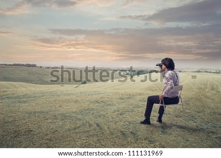 Businessman sitting on a chair on a green meadow and using binoculars