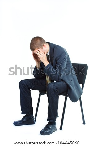 Businessman sitting on a chair with head between hands, looking down - isolated on white