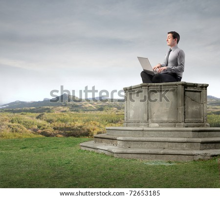 Businessman sitting on a pedestal and using a laptop - stock photo