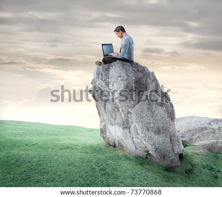 Businessman sitting on a rock and using a laptop