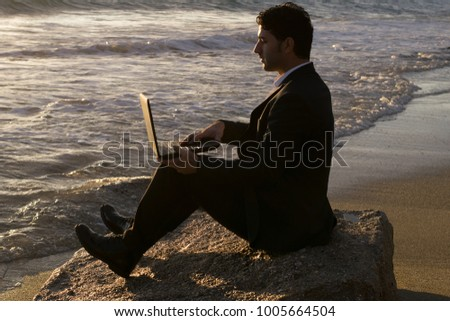 Businessman sitting on a rock by the sea and working on a laptop #1005664504