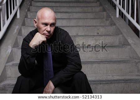 Businessman sitting on a staircase with his hand under his chin